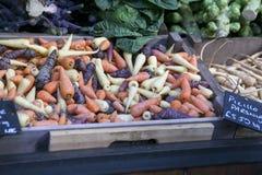 As cenouras vermelhas, brancas e azuis no mercado para a venda imagem de stock