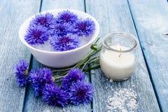 As centáureas azuis encontram-se na água em uma bacia branca perto de uma vela ardente na perspectiva das placas idosas azuis imagens de stock royalty free