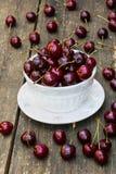 As cerejas frescas no vintage branco rolam na tabela de madeira velha Bagas maduras no fundo, dia de verão Imagens de Stock