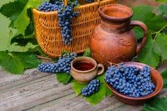 As cestas e a bacia com as uvas ao lado do frasco e do copo com vinho estão sobre na madeira rústica foto de stock royalty free