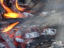 As chamas rastejam acima do lado de uma parte de lenha em uma fogueira aberta fotografia de stock