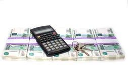 As chaves da calculadora e do apartamento em pacotes de dinheiro apresentaram em seguido bancos e conceito da hipoteca foto de stock