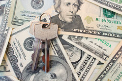 As chaves em um fundo do dinheiro O conceito de comprar ou de alugar uma casa Fotografia de Stock