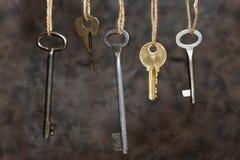 As chaves estão pendurando nas cordas em um fundo marrom-cinzento Chaves velhas Conceptual imagem de stock