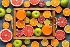 As citrinas cortadas colhem a configuração lisa da mistura na bandeja de madeira no fundo concreto azul, alimento biológico saudá imagens de stock