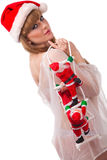 As cláusulas de Santa escalam acima da menina 'sexy' de Santa fotografia de stock