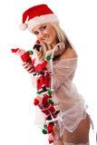 As cláusulas de Santa escalam acima da menina 'sexy' de Santa fotografia de stock royalty free
