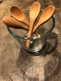 As colheres de madeira no vidro no assoalho do cimento com café iluminam-se Fotografia de Stock Royalty Free