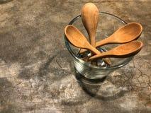 As colheres de madeira no vidro no assoalho do cimento com café iluminam-se Fotografia de Stock