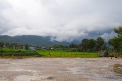 As comunidades com cenário natural com campos verdes, galinhas aumentaram na natureza com um fundo bonito da montanha com nuvens imagem de stock