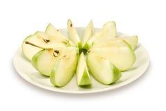 As configurações da maçã do verde do corte em uma placa Fotos de Stock Royalty Free