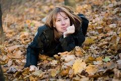 As configurações da mulher nova na madeira do outono Fotografia de Stock