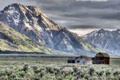 As construções históricas abaixo da neve tamparam montanhas no Tetons grande Fotografia de Stock