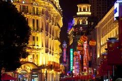 As construções iluminaram-se acima na noite com bandeiras chinesas foto de stock royalty free