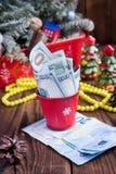 As contas torcidas dos dólares e dos euro no Natal vermelho bucket, euro- e bolinhos de amêndoa cor-de-rosa Presentes do ` s do a Fotos de Stock Royalty Free
