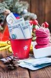 As contas torcidas dos dólares no Natal vermelho bucket, euro- e bolinhos de amêndoa cor-de-rosa Presentes do ` s do ano novo Imagem de Stock Royalty Free