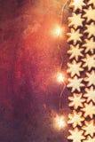 As cookies alemãs do Natal dirigem estrelas vitrificadas cozidas da canela com Garland Lights efervescente Nuts em Rusty Dark Bac foto de stock royalty free