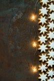 As cookies alemãs tradicionais do Natal dirigem estrelas vitrificadas cozidas da canela com Garland Lights efervescente Nuts em R fotos de stock