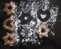 As cookies bávaras congelaram com pó do açúcar no fundo preto fotos de stock