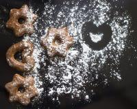 As cookies bávaras congelaram com pó do açúcar no fundo preto fotos de stock royalty free
