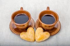 As cookies caseiros dão forma ao coração e aos copos fora do café Fotos de Stock Royalty Free