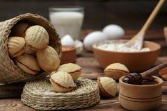 As cookies caseiros deram forma a porcas com leite condensado fervido creme na tabela de madeira Estilo rústico foto de stock