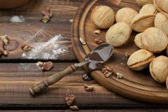As cookies caseiros deram forma a porcas com leite condensado fervido creme na tabela de madeira Estilo rústico colher com leite  imagens de stock