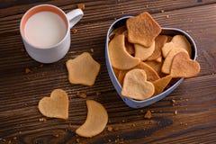 As cookies caseiros do gengibre no coração deram forma à caixa com um copo do leite Imagem de Stock