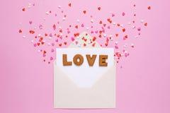 As cookies das letras amam com envelope e corações vermelhos no fundo cor-de-rosa imagens de stock royalty free