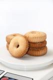 As cookies do chá arranjaram em uma escala digital para medir Fotografia de Stock Royalty Free