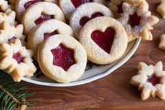 As cookies do Natal de Linzer arranjaram em uma placa em uma tabela de madeira Imagem de Stock Royalty Free