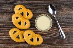 As cookies, leite condensado na bacia, dão na tabela de madeira foto de stock