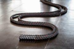 As cordas da batalha encontram-se no assoalho preto no gym da aptidão Foto de Stock