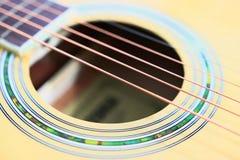 As cordas da guitarra acústica na tabela de madeira na sala, no fim acima da vista superior e na luz solar com espaço vazio para  Imagem de Stock Royalty Free