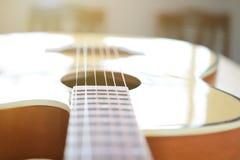As cordas da guitarra acústica na tabela de madeira na sala, no fim acima da vista superior e na luz solar com espaço vazio para  Fotos de Stock Royalty Free