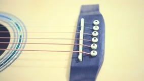 As cordas da guitarra acústica na tabela de madeira na sala, no fim acima da vista superior e na luz solar com espaço vazio para  Imagens de Stock