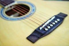 As cordas da guitarra acústica na tabela de madeira na sala, no fim acima da vista superior e na luz solar com espaço vazio para  Foto de Stock