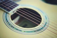 As cordas da guitarra acústica na tabela de madeira na sala, no fim acima da vista superior e na luz solar com espaço vazio para  Fotografia de Stock Royalty Free