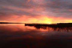 As cores brilhantes do fulgor do por do sol sobre a superfície do lago molham Imagens de Stock