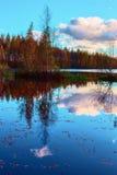 As cores brilhantes do outono refletiram nas águas imóveis de um lago bonito da floresta Fotos de Stock Royalty Free