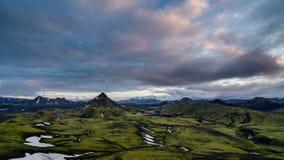 As cores do por do sol no céu nublam-se sobre a natureza islandêsa verde das montanhas Zumbe dentro a inclinação acima filme