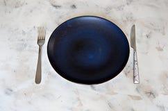 As cores pastel cerâmicas da placa da cutelaria bifurcam-se espaço da cópia do fundo do prato da faca fotos de stock royalty free