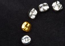 As coroas do dente do ouro dental e do metal no preto escuro surgem Imagens de Stock Royalty Free