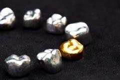 As coroas do dente do ouro dental e do metal no preto escuro surgem Imagem de Stock Royalty Free