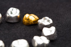 As coroas do dente do ouro dental e do metal no preto escuro surgem Fotos de Stock