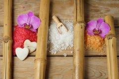 As corrediças do sal colorido para o banheiro em uma tabela de madeira com orquídea florescem as peças de bambu Foto de Stock Royalty Free