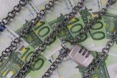 As correntes com combinação padlock em cédulas do Euro como o banco da segurança fotografia de stock royalty free