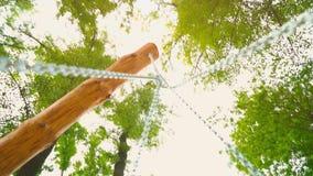 As correntes de aço resistentes para o balanço são unidas aos apoios de madeira, uma vista inferior vídeos de arquivo