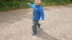 As corridas brincalhão do rapaz pequeno no jogo riem e sorriem vídeos de arquivo