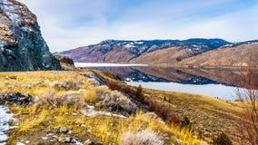 As corridas da estrada do transporte Canadá ao longo do lago Kamloops com as montanhas circunvizinhas que refletem no silêncio su Imagem de Stock